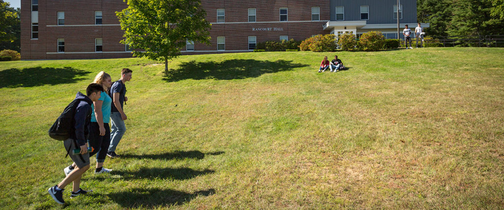 Students hanging out on lawn in front of Rancourt Hall residence hall