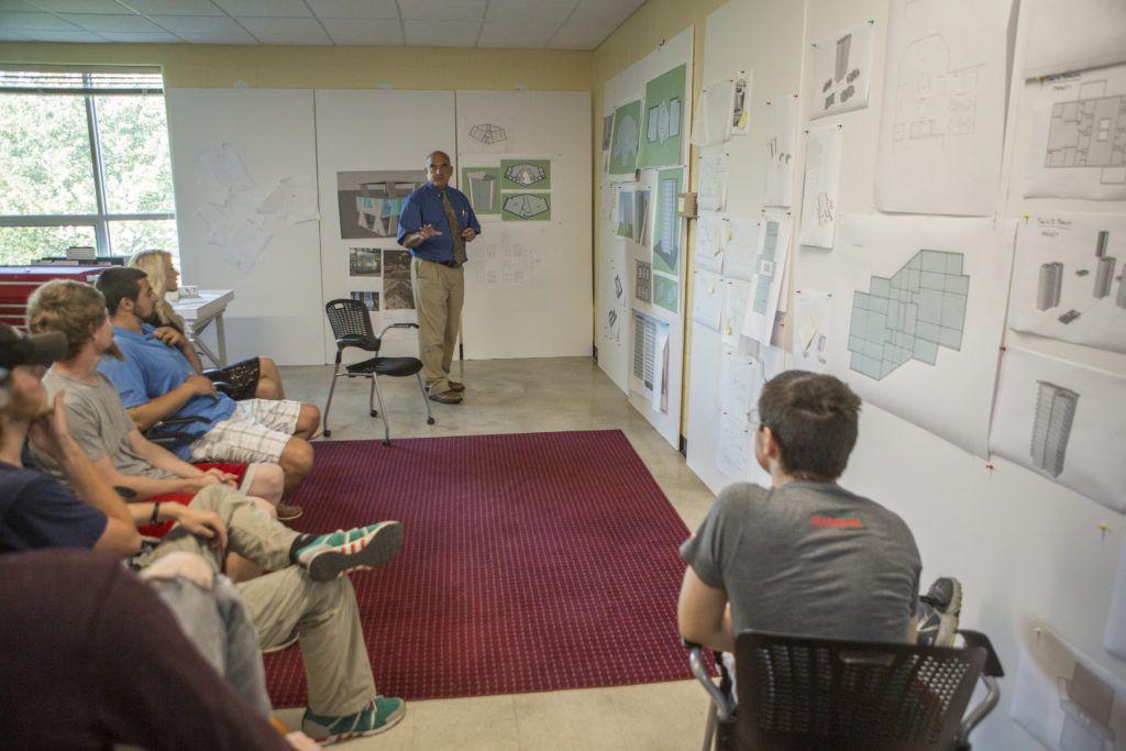 Students and an instructor take part in a design critique as part of the Architectural and Civil Engineering at Central Maine Community College.