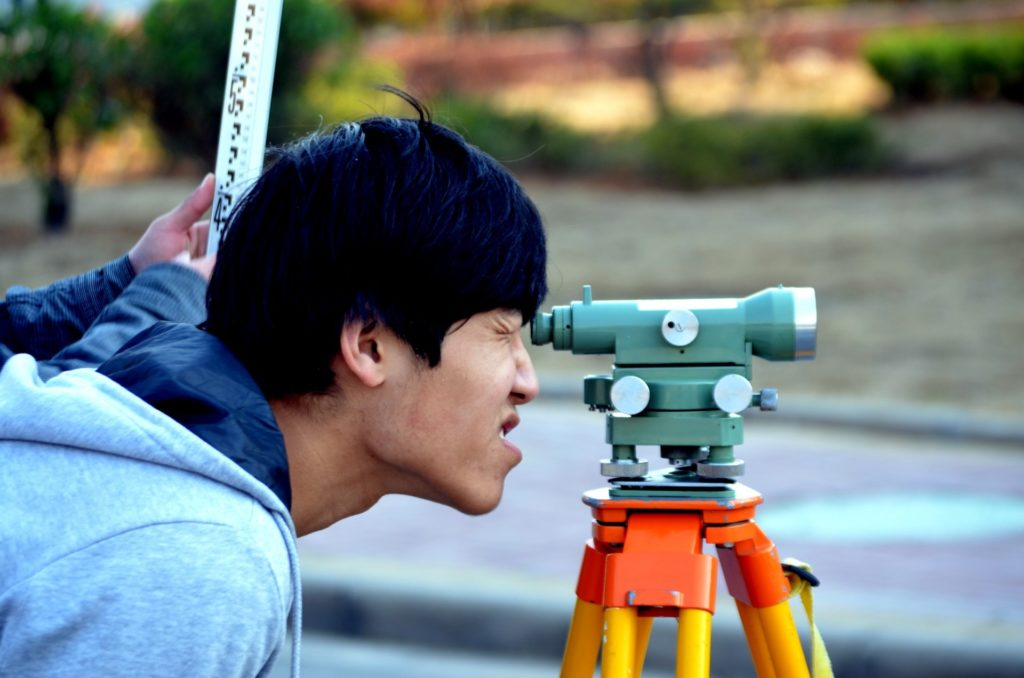 Individual looking through surveying equipment