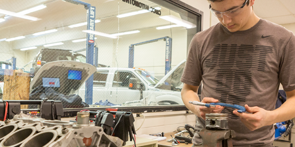 A student works on an engine in the Automotive Lab at Central Maine Community College