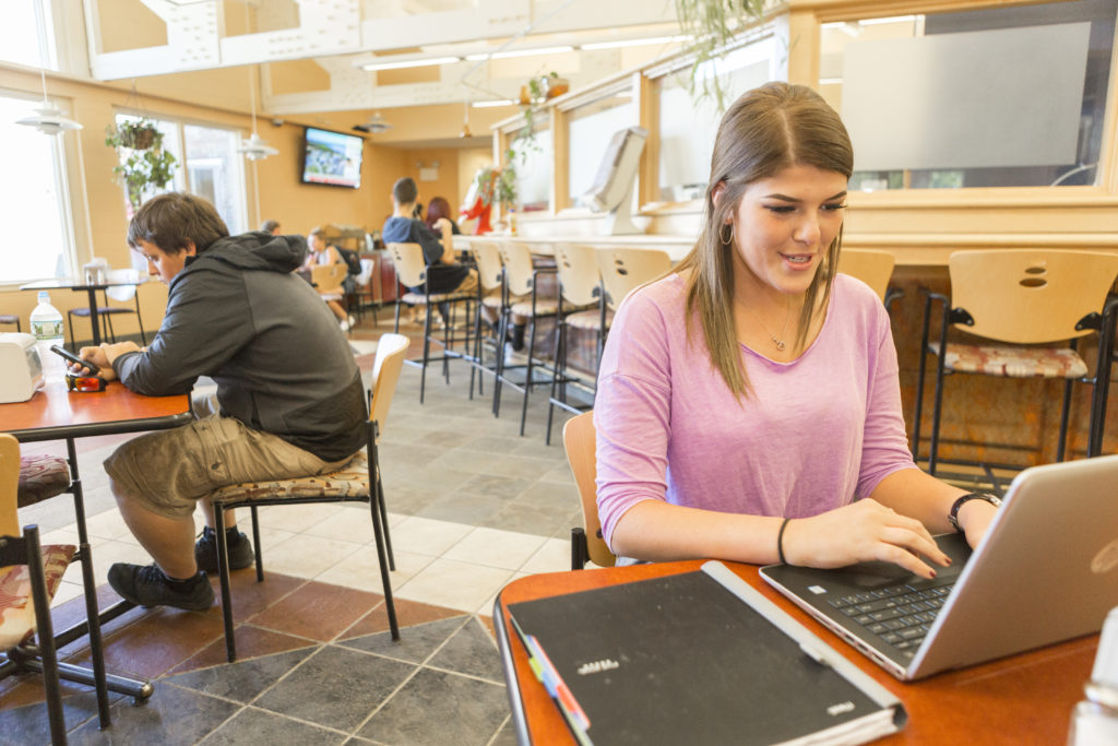 Dining Commons female in pink shirt studying