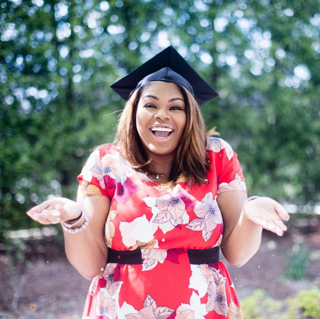 Excited female in red floral dress and graduation cap