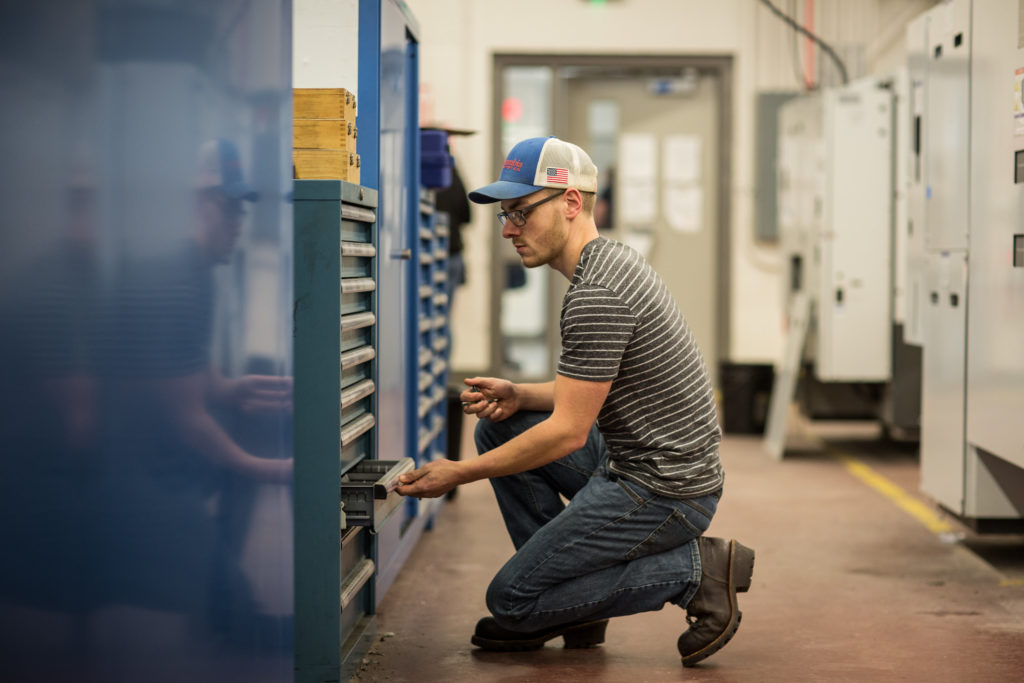 A male student gathers materials needed to complete a project in the Precision Machining Technology lab at Central Maine Community College.