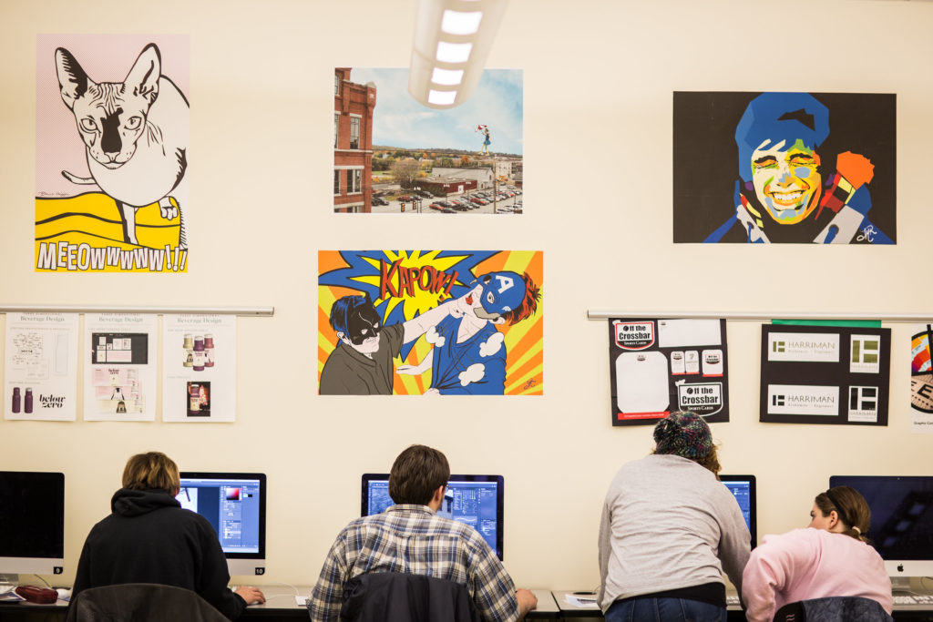 Students in the Design Lab working in Apple Computers and with the Adobe Creative Suite; the room is decorated with bright student designs in the pop style