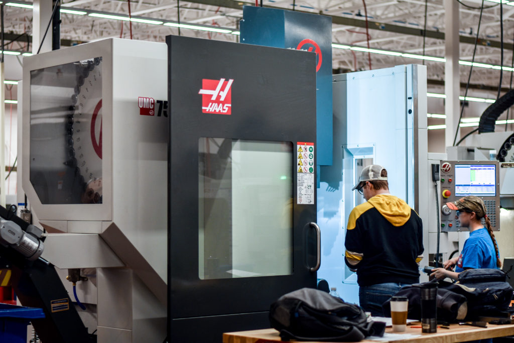 A male student works with a state-of-the-art 5-axis computer numerical control (CNC) machine in the new Precision Machining Technology lab at Central Maine Community College.