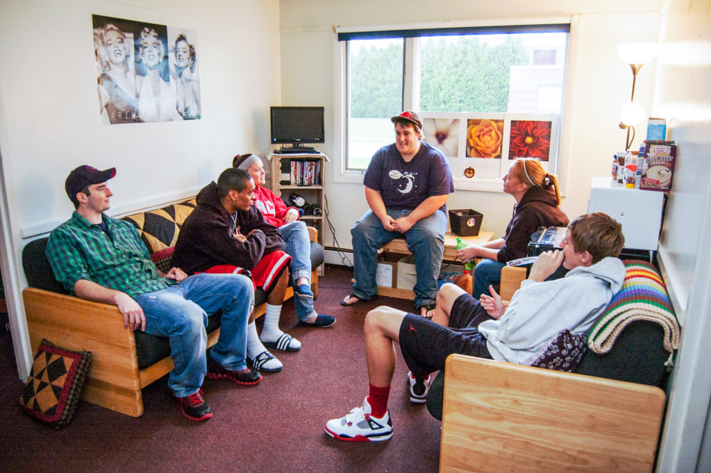 A large group of students hang out in the common area of an apartment on campus.