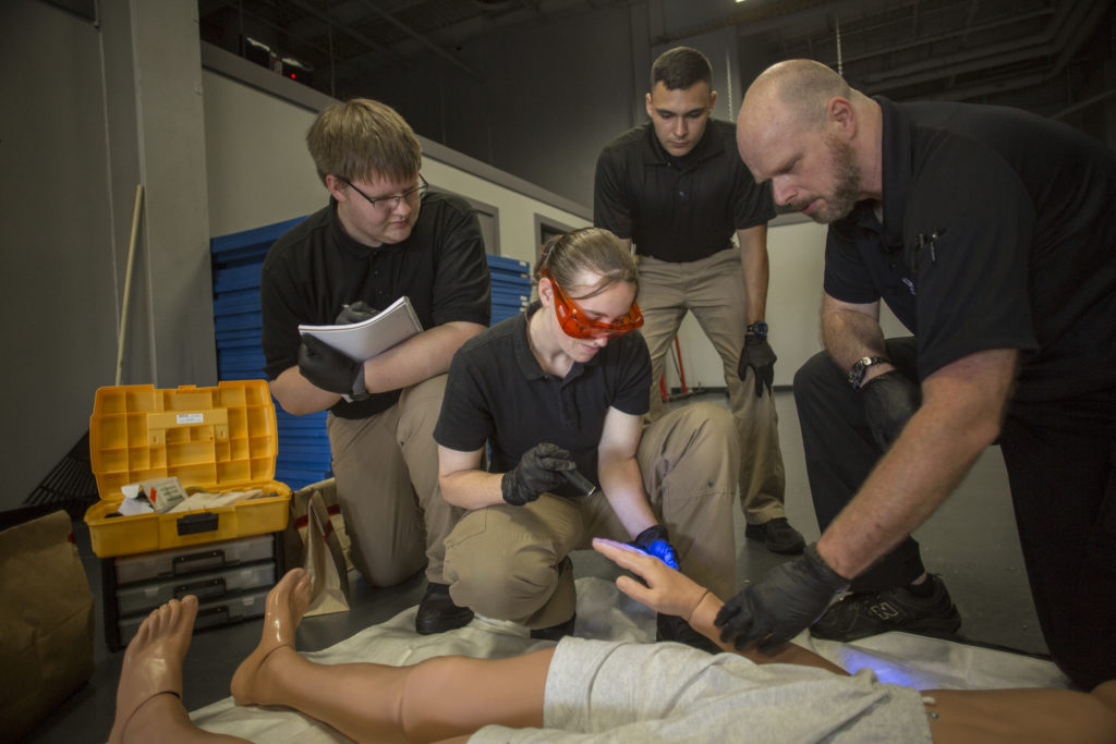 Students in the Forensic Science degree at Central Maine Community College analyze a staged indoor crime scene with human dummy.