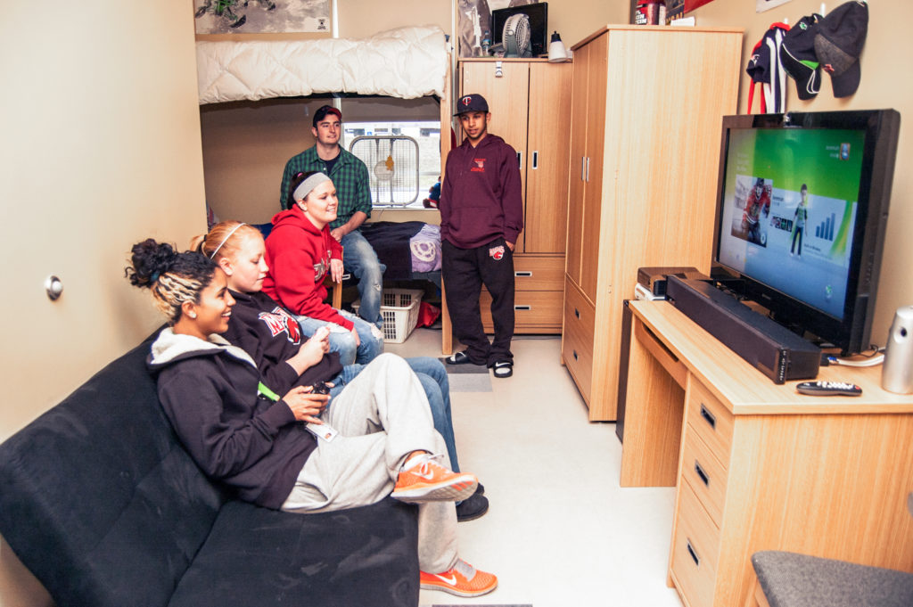 Students gather together in Rancourt Hall to take a break from studying and play a video game.