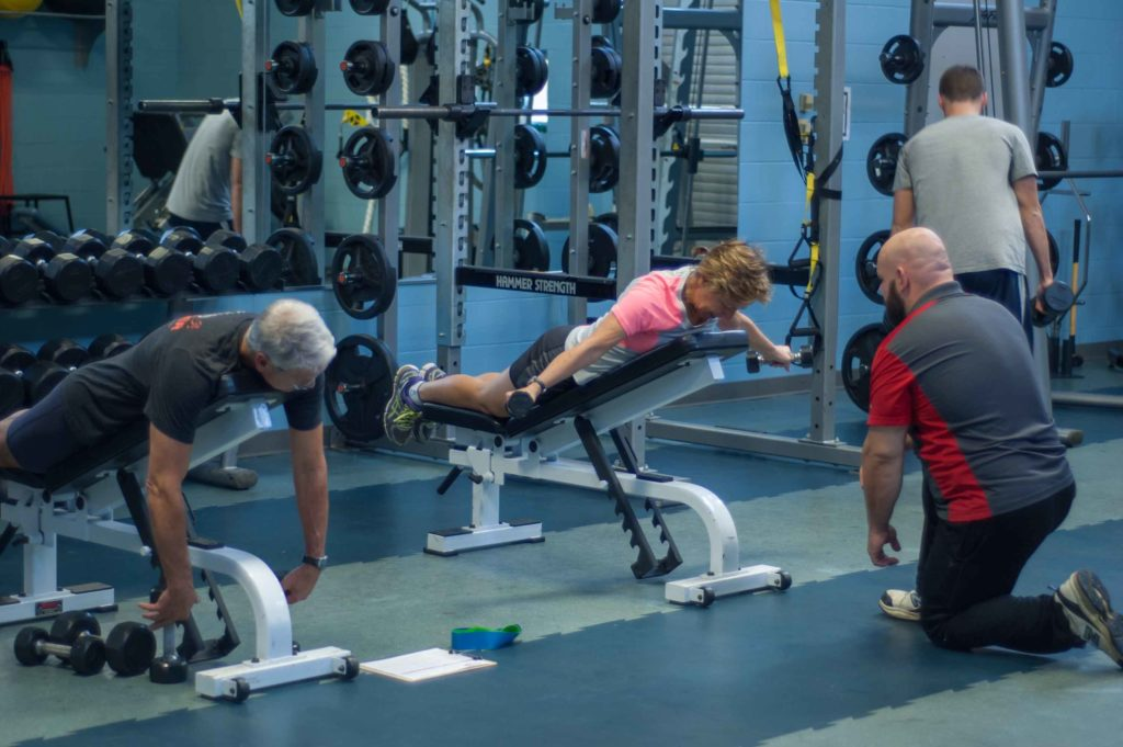 A male and female utilize a professional personal trainer in the Mustang Fitness Center at Central Maine Community College.