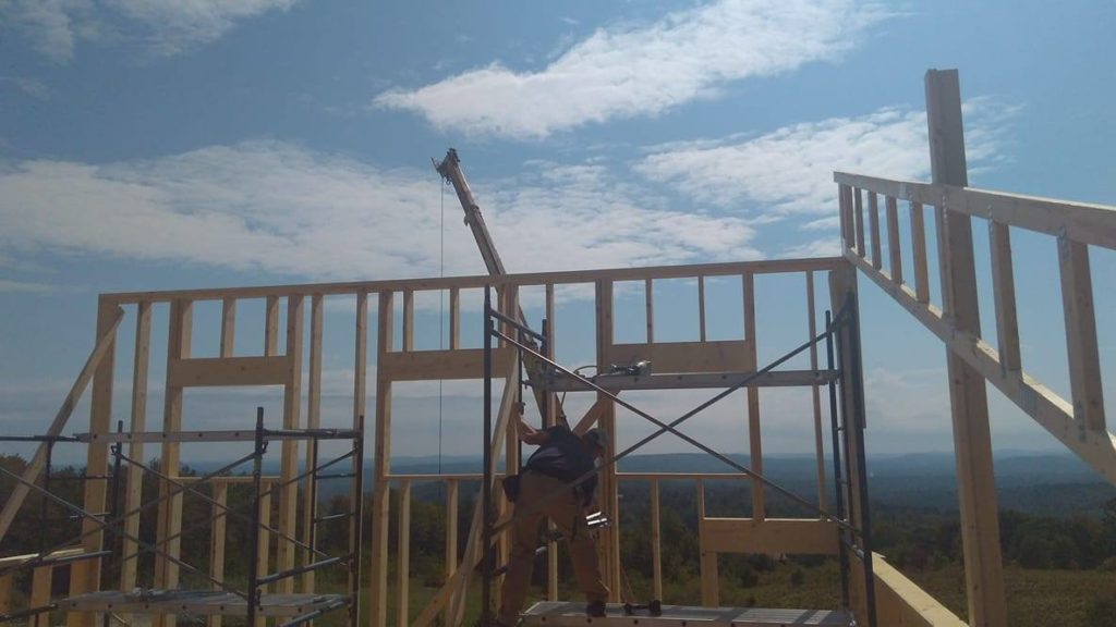 A student in the Building Construction Technology Jobsite degree at Central Maine Community College gains paid on-the-job training framing up a wall, overlooking beautiful mountains