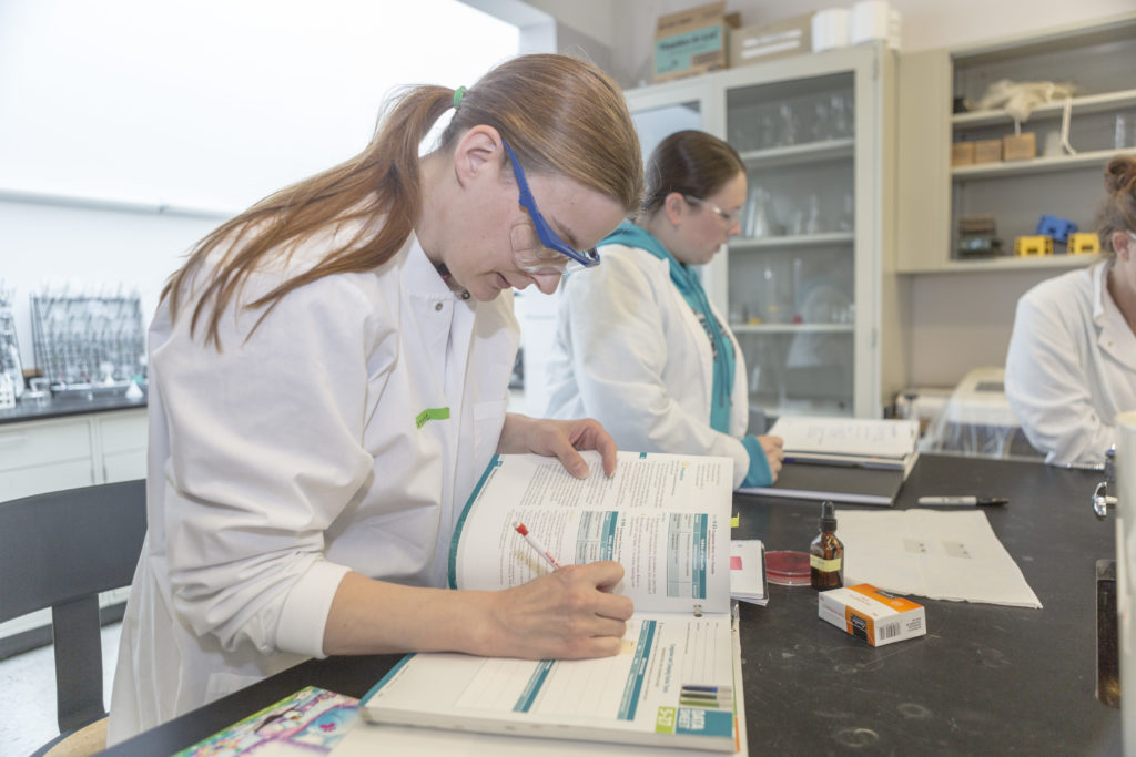 A female student in a science lab setting, in a lab coat and safety glasses, reviewing a scientific textbook