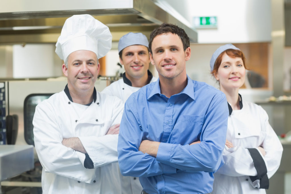Restaurant manager with culinary staff in a professional kitchen.