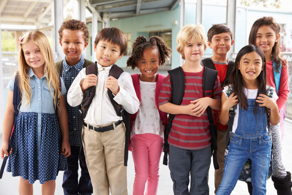 A group of young school-aged children with backpacks pose for a smiling photo