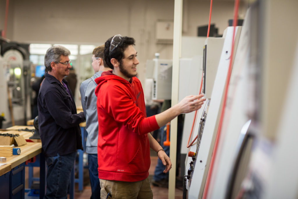 Male in a red sweatshirt at a CNC machine in the Precison Machining Technology lab