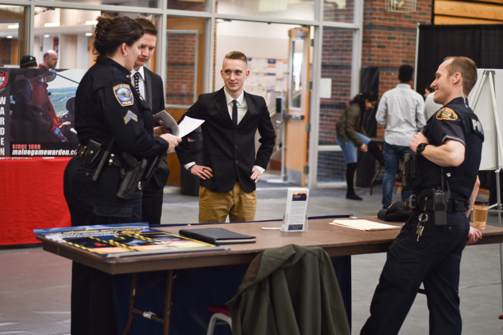 Three police officers and a criminal justice student attend the Criminal Justice Club Job Fair