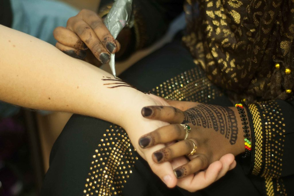 A student from the Muslim Student Association does henna on another student's arm