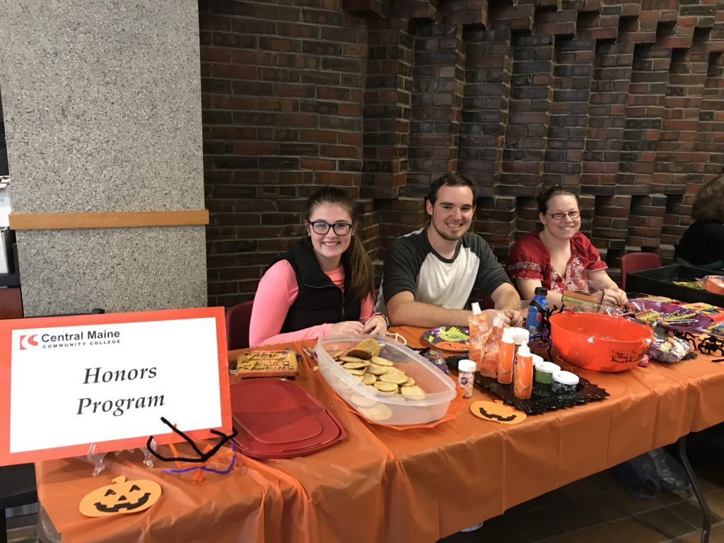Three members of the honors society host a table full of treats at the annual Halloween Fair