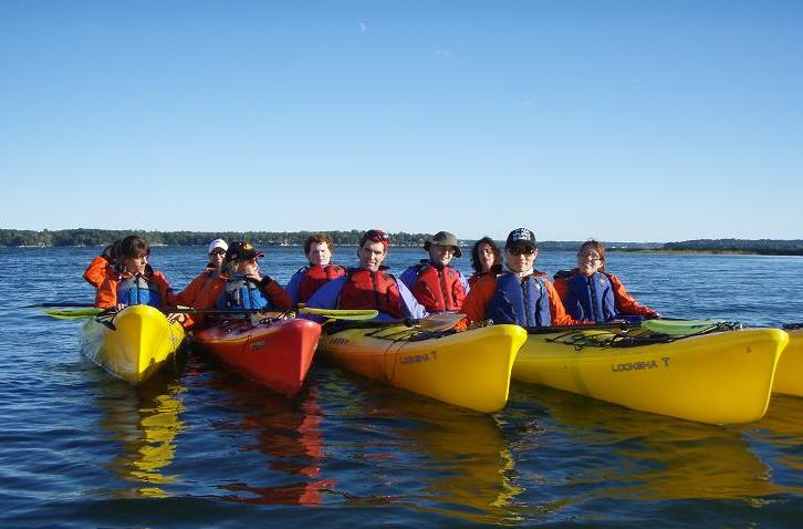Members of the Outdoor Club kayaking on a bright blue day and calm water