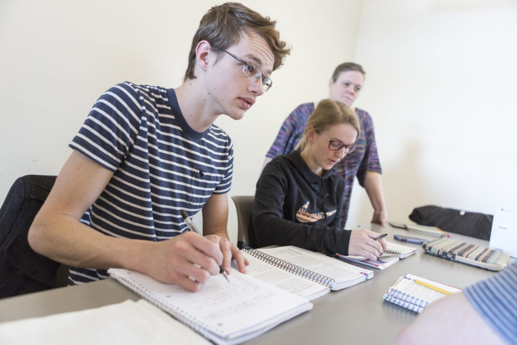 A male student takes notes during a class while two other individuals participate in the background.