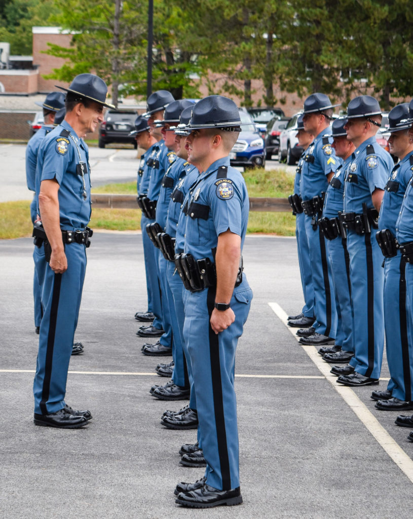 Colonel John Cote, left, chief of the Maine State Police, speaks to troopers during the official Troop B inspection held recently at Central Maine Community College