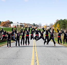Women's Basketball Champions jump in front of Central Maine Community College in their black and red warmup suits.