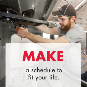 "Young white male with a beard, in a gray t-shirt, black baseball hat, and safety glasses changes a bit out on a CNC machine. Text overlay says ""Make a schedule to fit your life."""